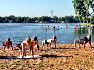 Doing yoga on the beach at GetKnit Events Paddleboard Bootcamp