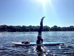Doing yoga on a paddleboard at getknit events paddleboard bootcamp